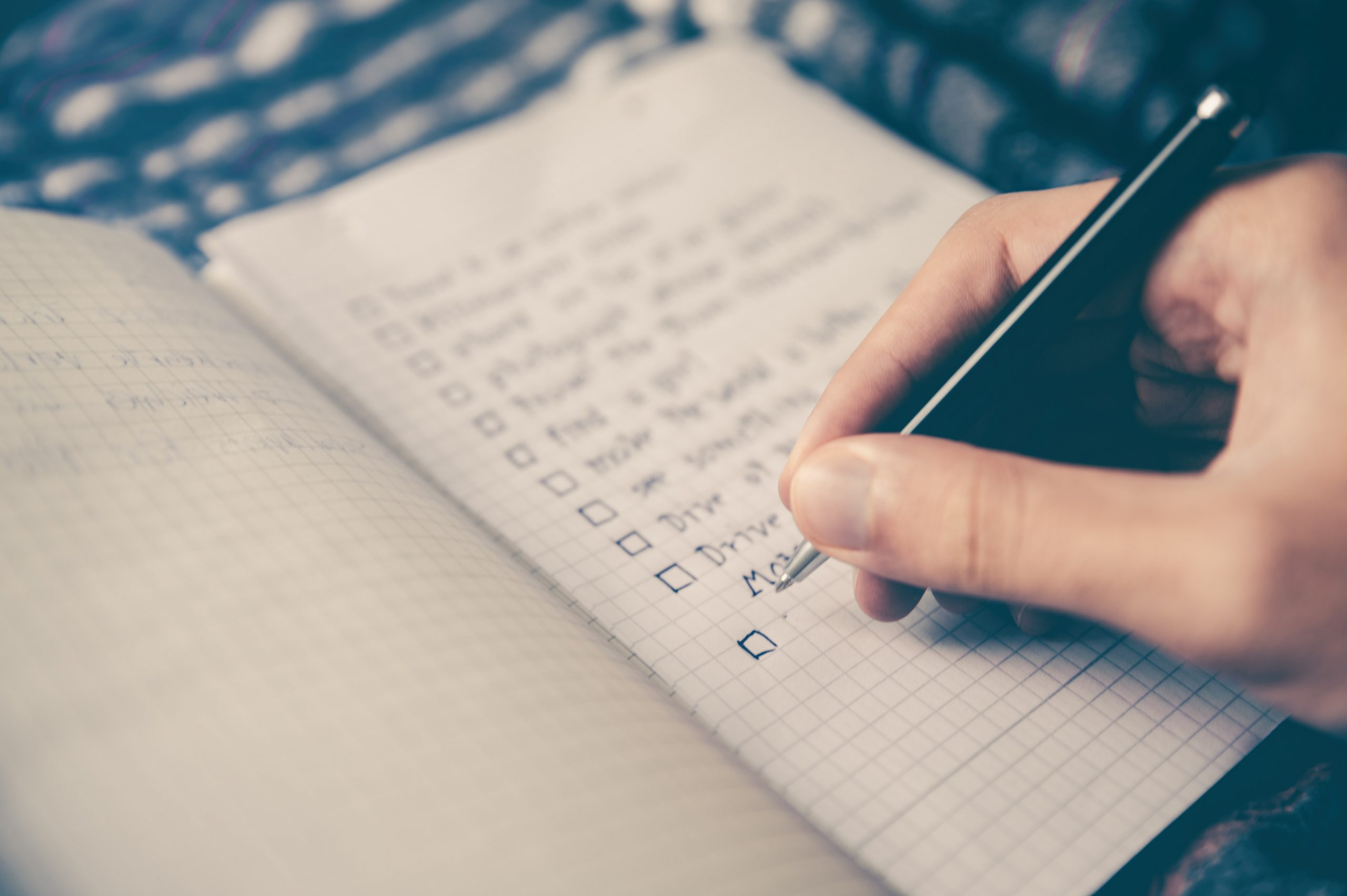 Close up of someone's hand writing a checklist in a notebook