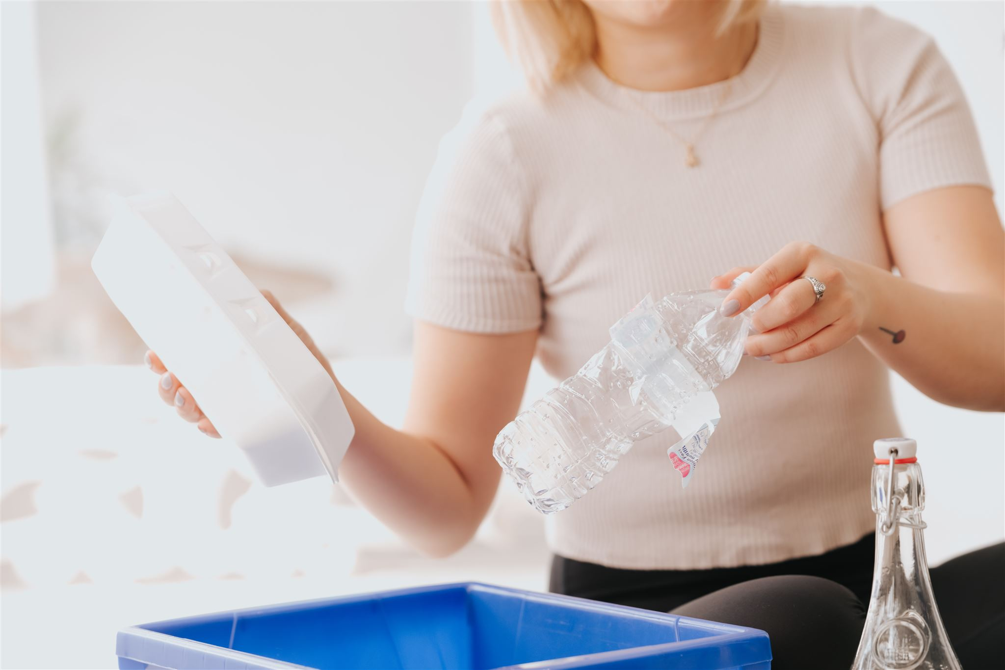 Woman holding a styrofoam container and plastic water bottle over a blue recycling bin