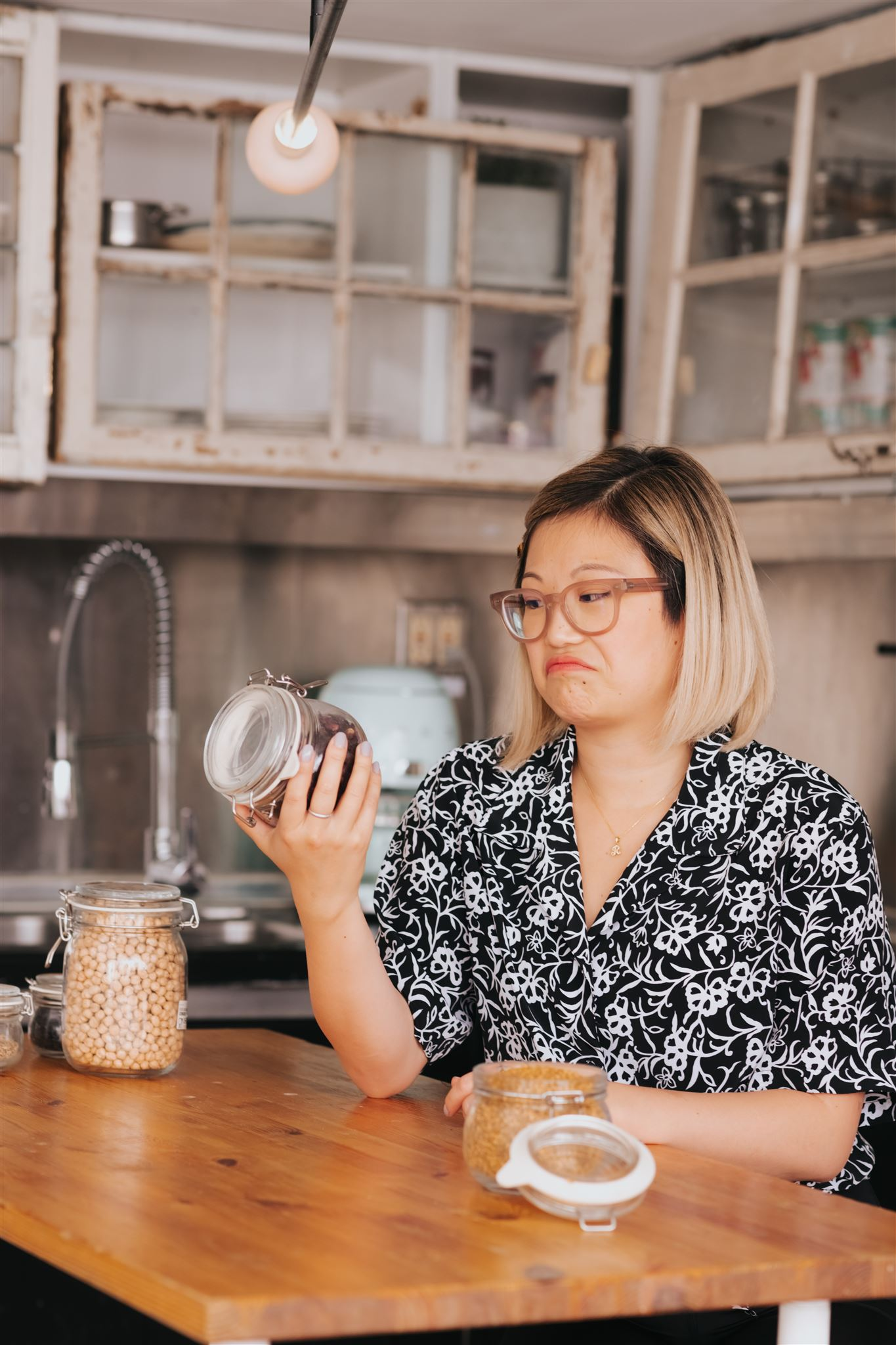 Woman sitting at a table holding up and examining a glass jar of almonds