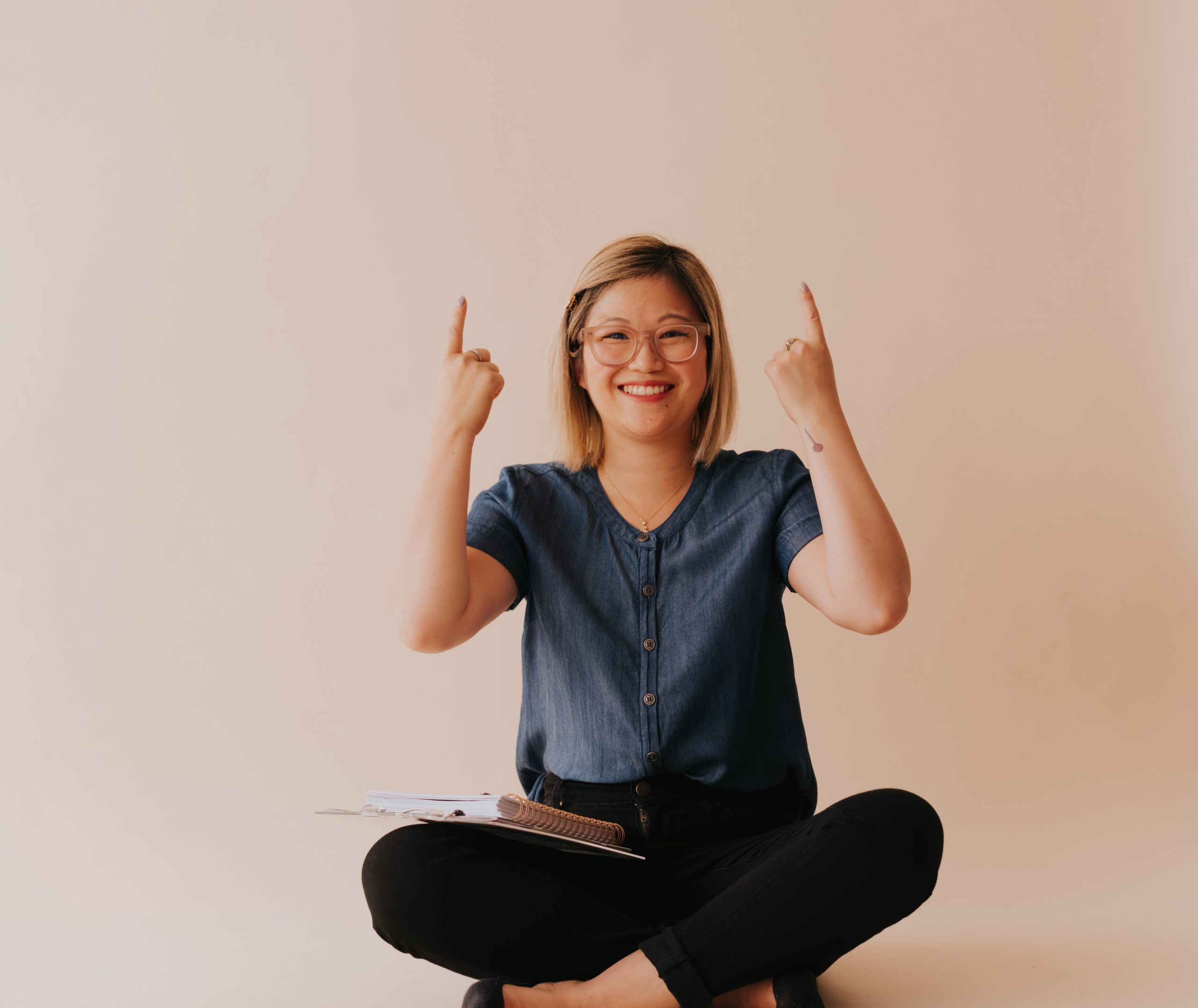 Woman sitting cross-legged on the floor pointing up with both index fingers