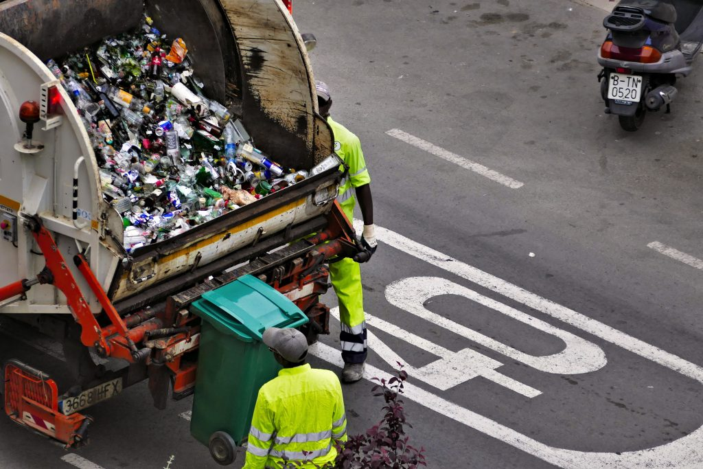 Bird's eye view of the back of a garbage truck with two employees dumping the contents of a bin into the truck