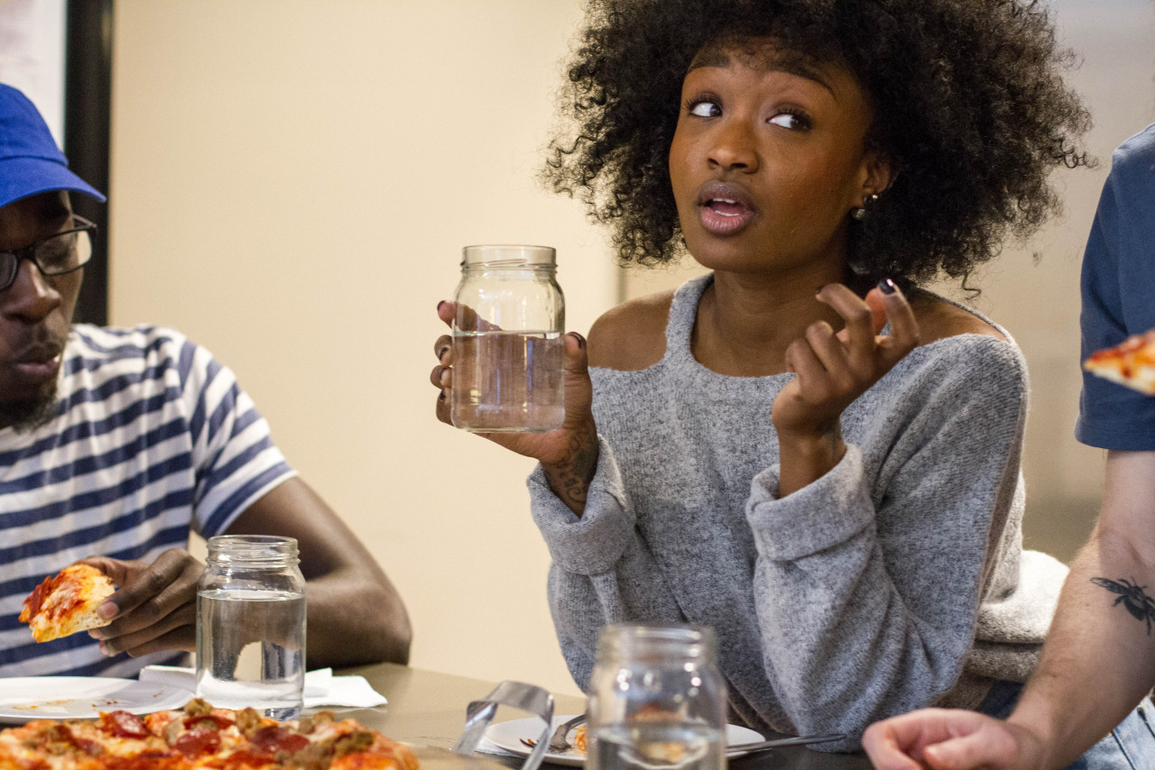 Black woman holding a mason jar of water looking surprised