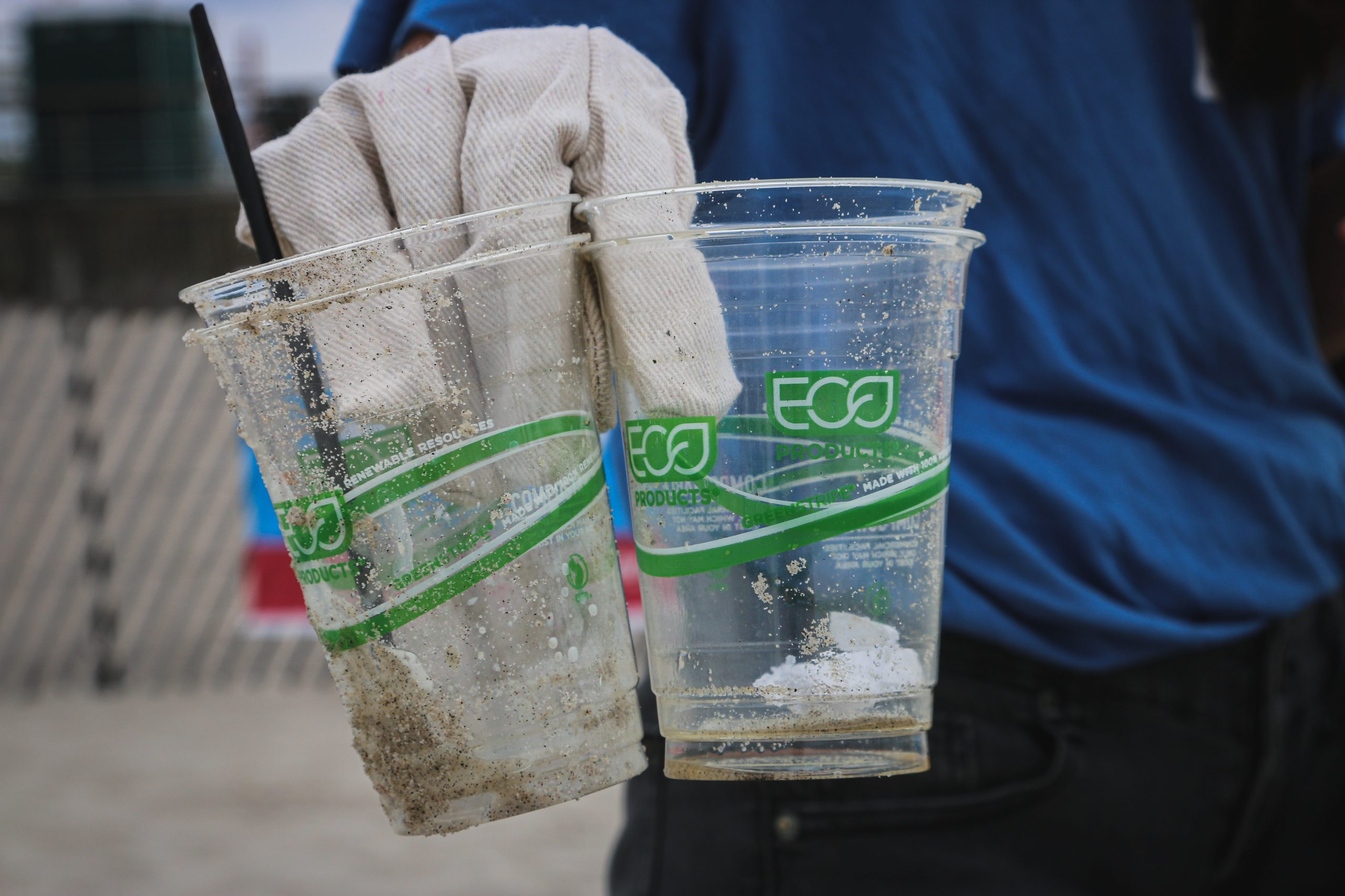 Person holding a few bio-plastic cups found on the beach with sand and plastic straw