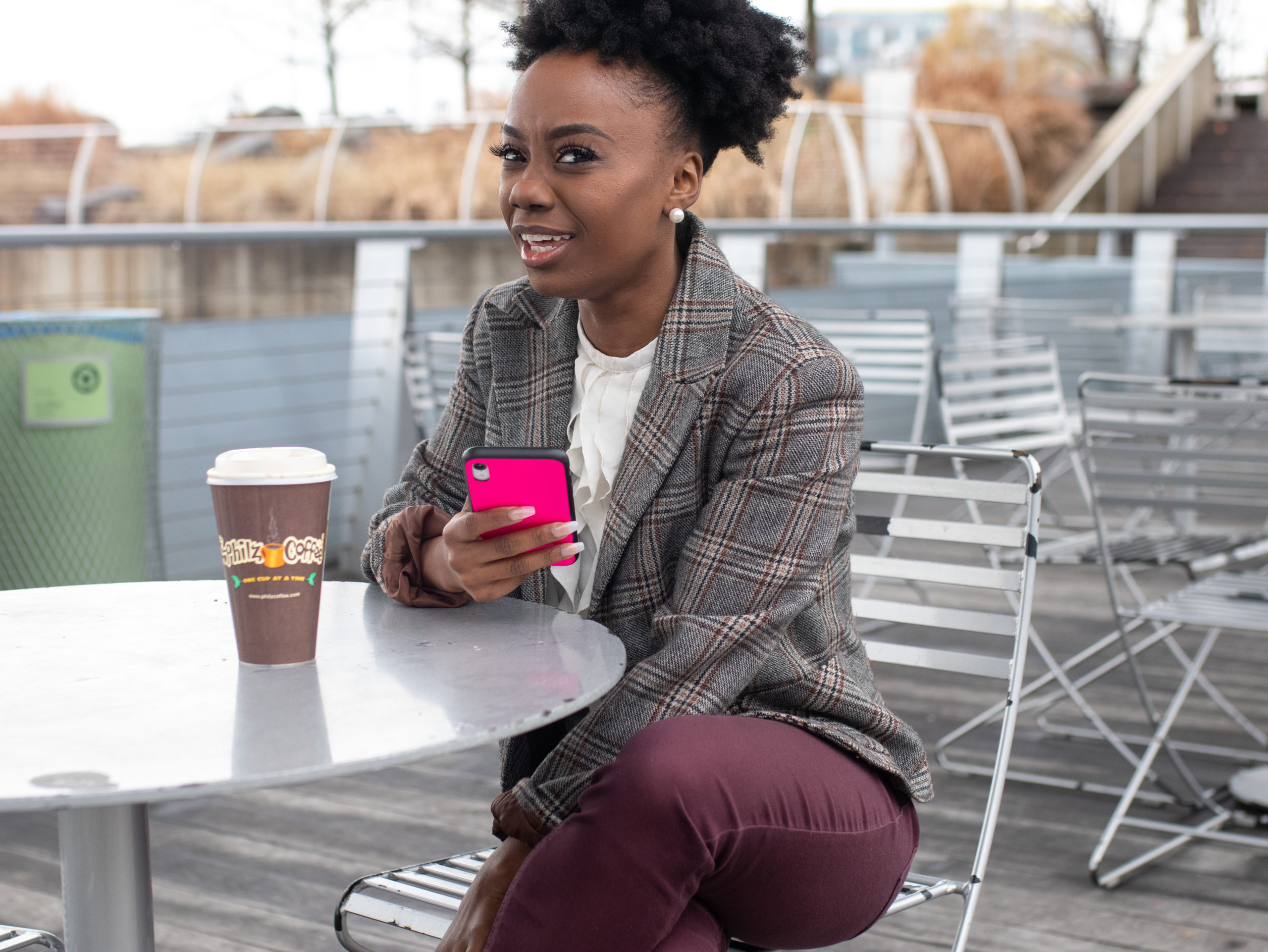Black woman sitting outside on a patio with a confused look on her face, holding a neon pick phone and disposable coffee cup at the table