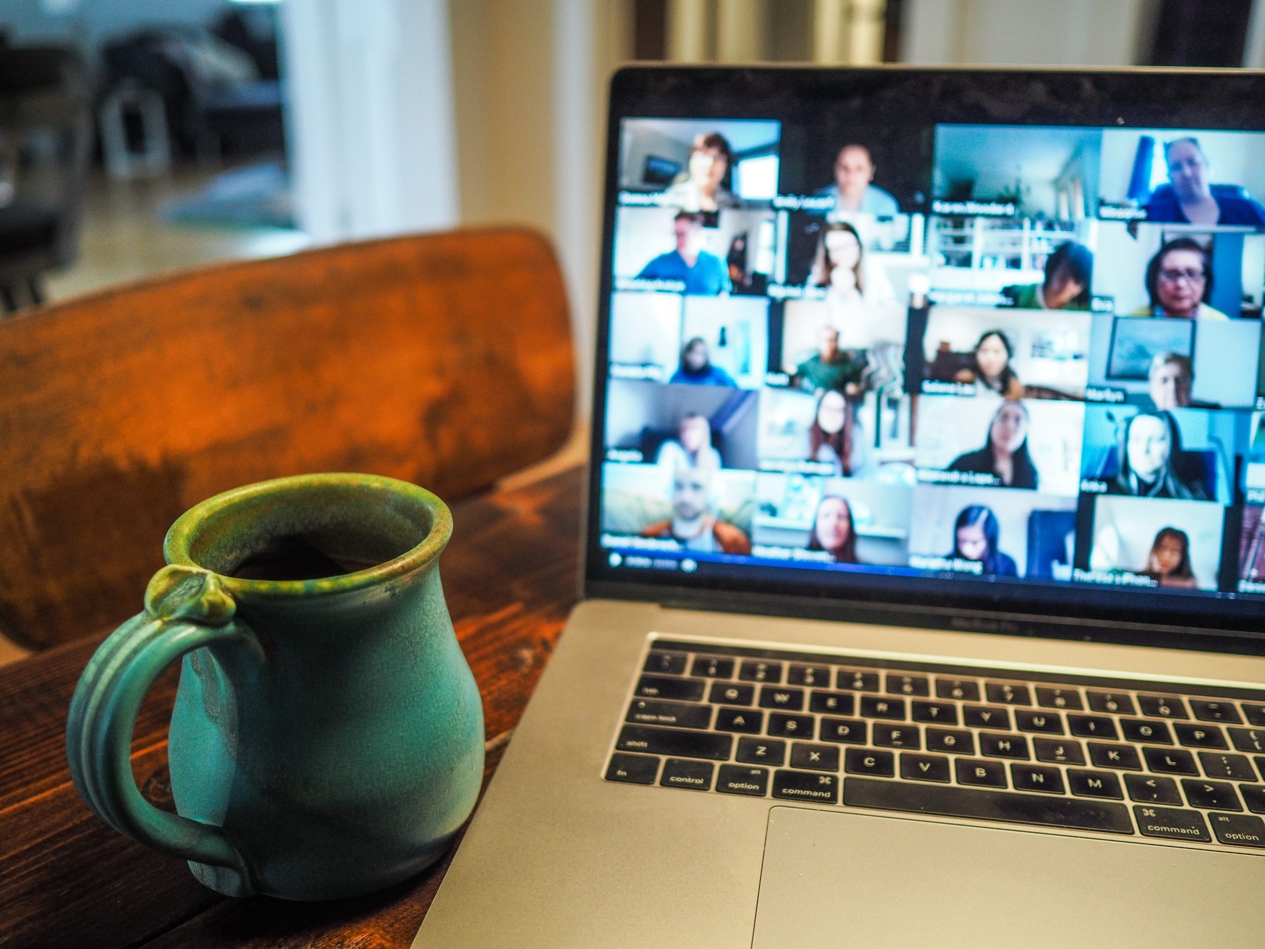Turquoise mug next to a laptop with a large video call on screen