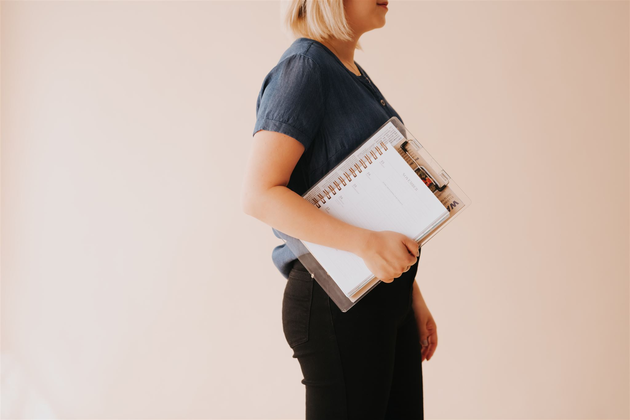 Side profile of a woman holding a clipboard and notebook