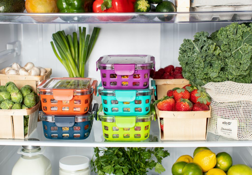 Inside a fridge with produce in bags, food in tupperware containers