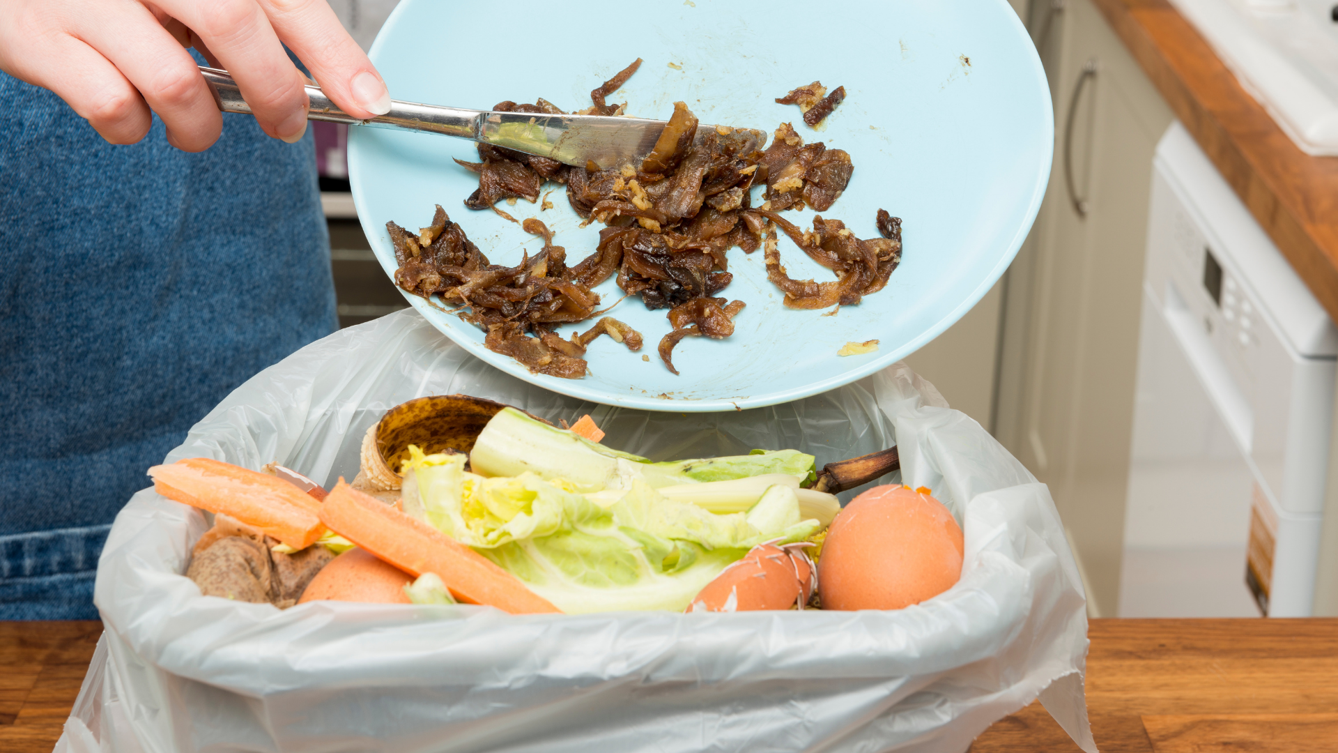 Food scraps being scraped into an organics bin with other foods
