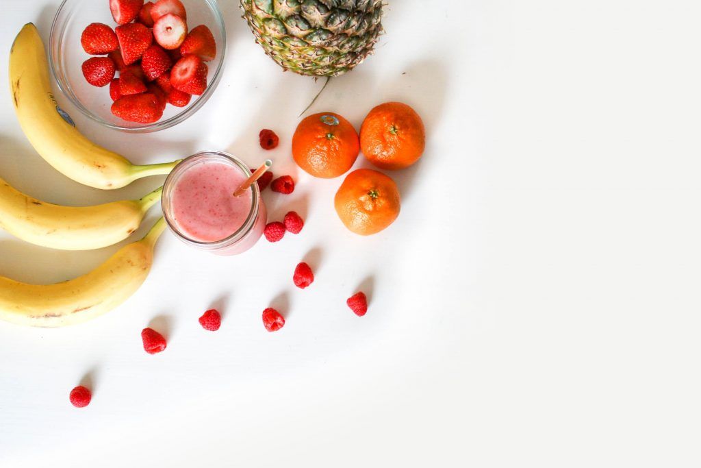 Fruit spread with bananas, strawberries, pineapple and oranges with a smoothie cup