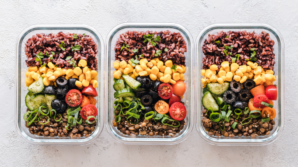 Three identical glass containers of food, meal prepping