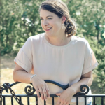 Headshot of Emily with arms resting on a fence