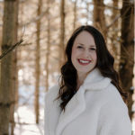 Headshot of Holly in a white furry coat in the snowy woods