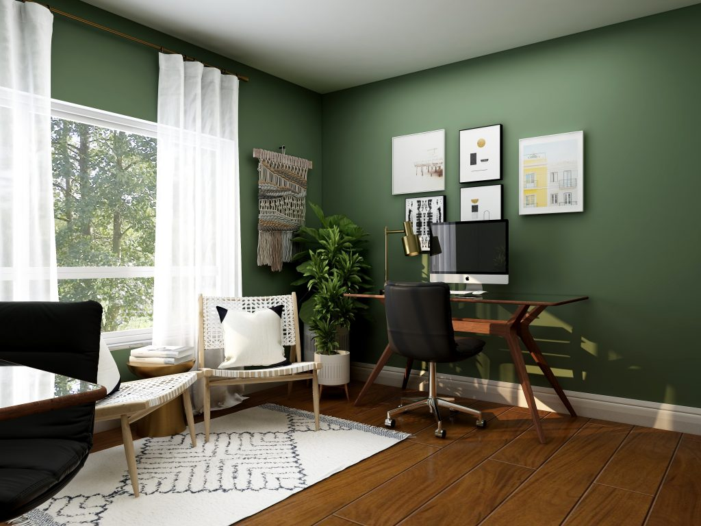 Home office with green walls, desk and chair, white curtains and paintings on wall