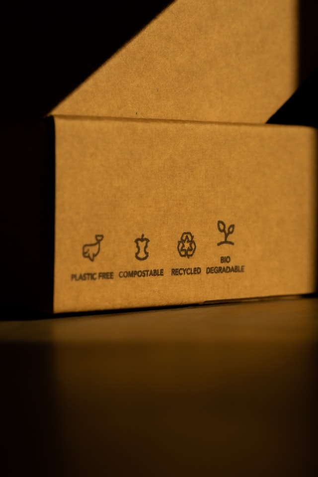 Close up of the size of a box with labels that say plastic-free, compostable, recycled and biodegradable